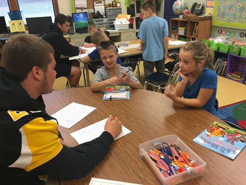 High School students visit 2nd grade classrooms as part of Tackling Illiteracy.